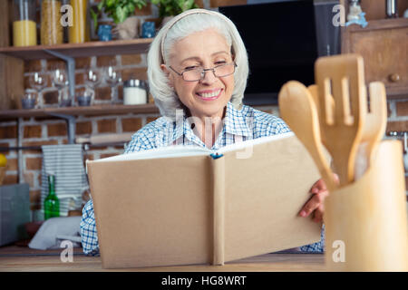 Smiling senior woman in eyeglasses reading cookbook in kitchen - Stock Photo
