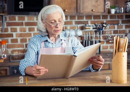 Senior woman in eyeglasses reading cookbook in kitchen - Stock Photo