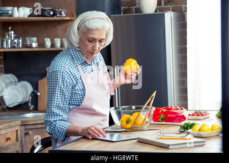 Senior woman using digital tablet in kitchen while preparing vegetable salad - Stock Photo