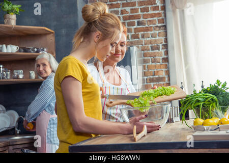 Happy family cooking together vegetable salad in kitchen - Stock Photo