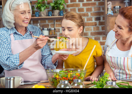 Young woman tasting fresh vegetable salad while standing with mother and grandmother in kitchen - Stock Photo
