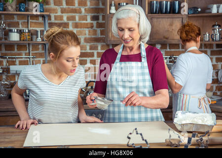 Grandmother and granddaughter sifting flour for cookies in kitchen - Stock Photo