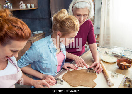 Happy family of three generations preparing gingerbread cookies at home - Stock Photo