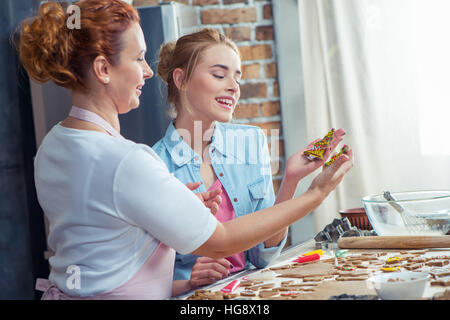 Mother and daughter making Christmas cookies in kitchen - Stock Photo