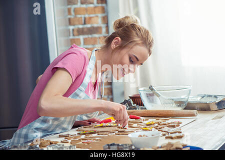 Teenage girl wearing apron and icing Christmas cookies - Stock Photo