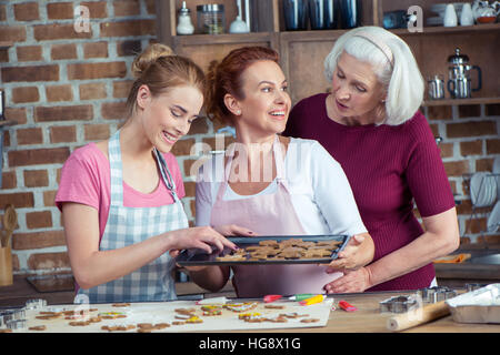 Happy family of three generations making Christmas cookies together - Stock Photo