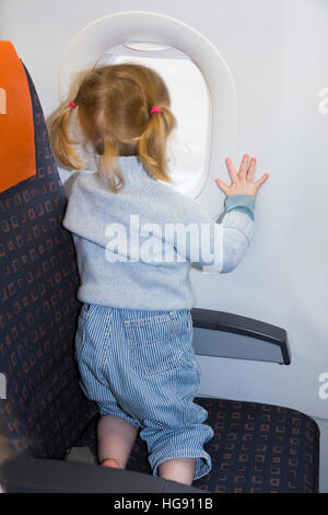 Child / toddler children age 2 on holiday vacation looking looks look out window flying on air plane / airplane - Stock Photo