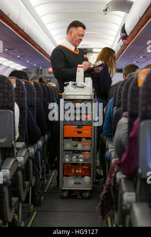 Cabin crew / air steward serves drinks and snacks to passengers – & takes payment – from a trolley cart during an Easyjet flight