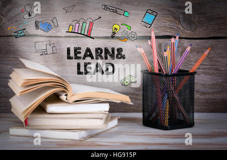 Learn and Lead. Stack of books and pencils on the wooden table. - Stock Photo