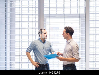 Two colleagues speaking together about project documents standing in bright modern office interior - Stock Photo