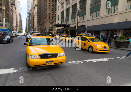 NEW YORK - APRIL 28, 2016: Typically yellow medallion taxicabs in front of Macy's department store. They are widely - Stock Photo