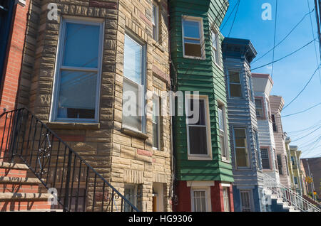 facades of typical american townhomes with front stairs in jersey city - Stock Photo