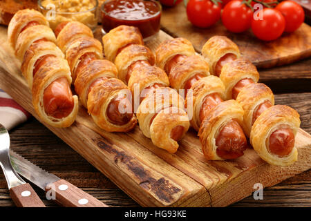Rolled hot dog sausages baked in puff pastry on wooden background - Stock Photo