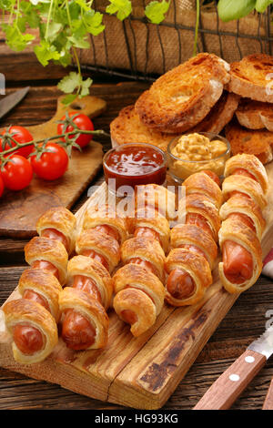 Rolled hot dog sausages baked in puff pastry and salad on wooden background - Stock Photo