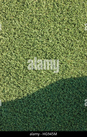 Artificial grass fake turf synthetic lawn field macro closeup with gentle shaded shadow area, green sports texture - Stock Photo