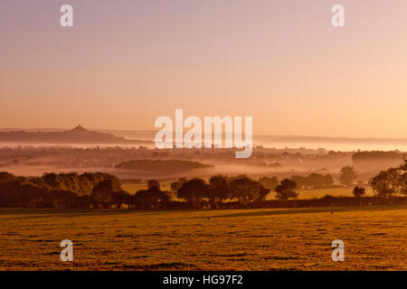 An early morning sunrise and mist filled hollows around Glastonbury Tor in Somerset, England, UK - Stock Photo