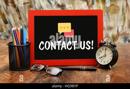 Contact Us with Communication Icon office supplies concept. - Stock Photo