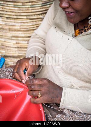 Ethiopian woman makes Habesha baskets for sale on a local market in Addis Abeba. - Stock Photo