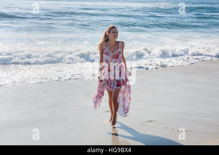 Young woman wearing a floral dress at the beach, La Jolla, California - Stock Photo