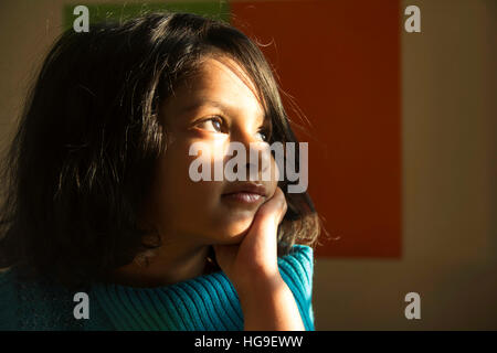 Close-up of cute little Indian girl dressed in blue looking towards the light - Stock Photo