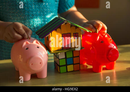 Baby girl putting coins in her piggy banks with magic square cube and small house - Stock Photo