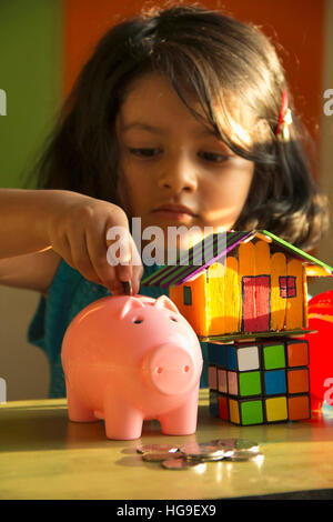 Baby girl putting coins in her piggy bank with magic square cube and small house - Stock Photo