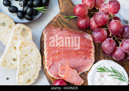 Cured meat, fresh baguette, grapes, cheese and black olives. Italian antipasti set. Close up view - Stock Photo
