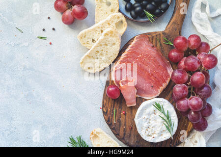 Appetizer plate with fresh baguette, cured meat, grapes, cheese and olives. Antipasti or tapas concept. Top view, copy space