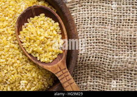 Bulgur, wheat grains. Raw uncooked bulgur in wooden spoon on linen textile background. Copy space for text. Healthy - Stock Photo