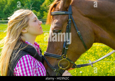 Young woman loves her horse - Stock Photo