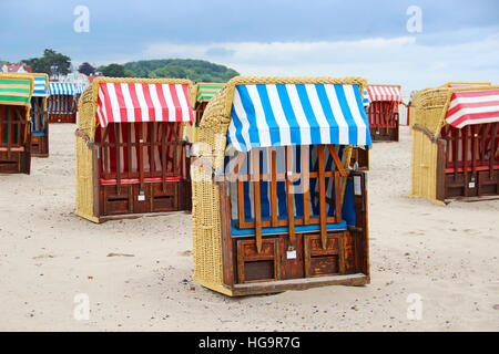 Strandkorb typical Baltic sea beach chairs in Travemunde, Germany - Stock Photo