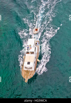 Fishing trawler on blue sea aerial vertical view - Stock Photo