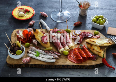 Mix of different snacks and appetizers. Spanish tapas on a black stone background.  bar. Space for text. Deli, sandwiches, - Stock Photo