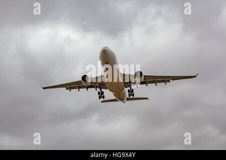 Passenger jet airplane low in the sky preparing to land - Stock Photo