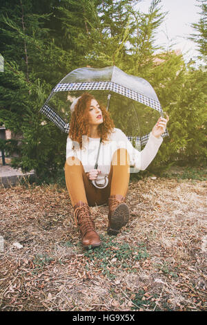 Young beautiful redhead woman with her transparent umbrella - Stock Photo