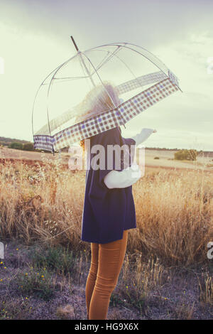 Woman with a transparent umbrella y a sunny autumn day - Stock Photo