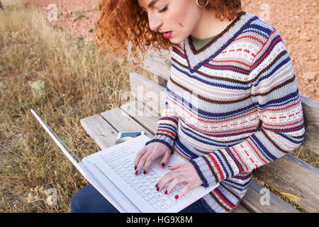 Young redhead freelance woman working with her laptop - Stock Photo