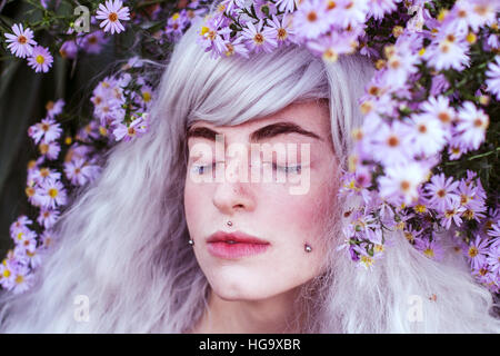 Young beautiful woman with white hair surrounded by little purple flowers - Stock Photo