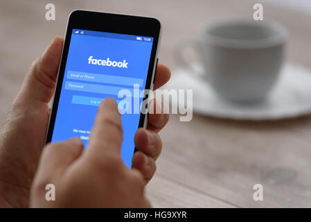 Krynica Poland - September 23, 2016: Smartphone in the hand when logging into Facebook applications. Facebook is - Stock Photo
