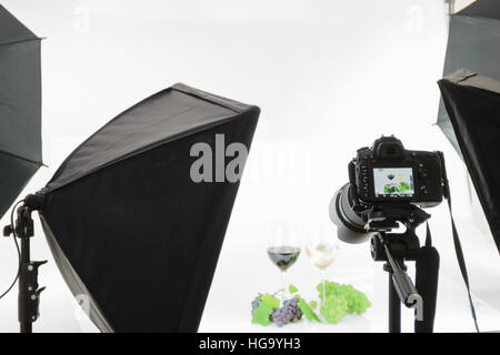 Professional SLR camera on a tripod takes a shot in the studio. - Stock Photo