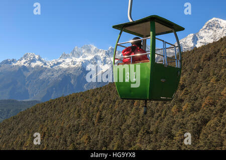 Lijiang, China - November 11, 2016: Cable Car on foreground with some tourists inside and Jade Dragon Snow Mountain - Stock Photo