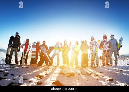 Group friends ski skiers snowboarders winter sports - Stock Photo