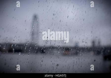 Raindrops on glass with blured london skyline at the background - Stock Photo