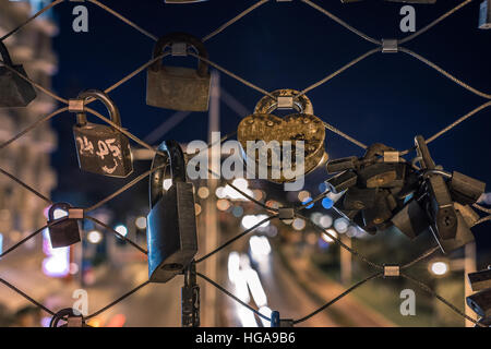 Locks on a metal wire fence with car light trails in the background - Stock Photo