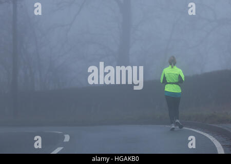 A female jogger wearing Hi Viz while jogging along the B4343 as the thick fog hampers visibility this morning. © - Stock Photo