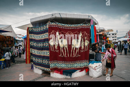 Traditional street market in Otovalo, Ecuador, full of textiles, fruit and vegetables, spices, jewerly and indigenous - Stock Photo