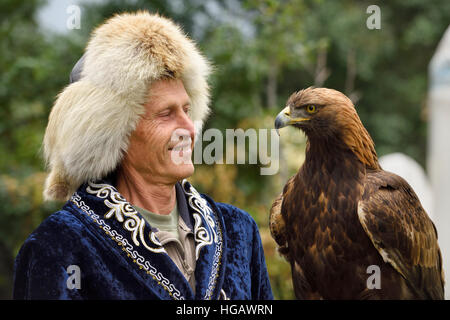 Professional trainer smiling at Golden Eagle at Sunkar Raptor Center in Alma Arasan Gorge Almaty Kazakhstan - Stock Photo