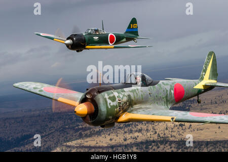 A Japanese A6M Zero and a Ki-43 Oscar fly above Madras, Oregon. - Stock Photo