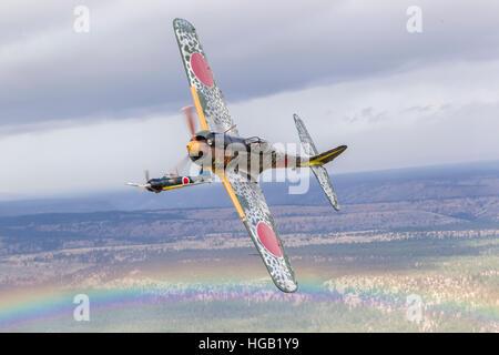 A Ki-43 Oscar breaks left while the A6M Zero holds in position over a rainbow near Madras, Oregon. - Stock Photo