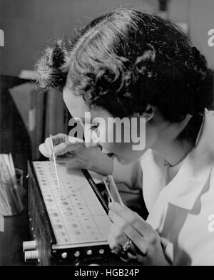 Laboratory technician displaying blood sample typing, 1957. - Stock Photo